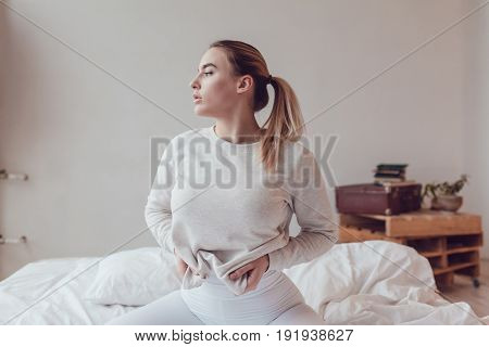 Sexy blonde woman in a grey sweatshirt sits on the bed. Mock-up.
