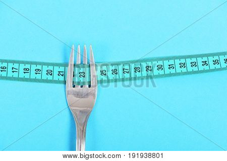 Cyan Blue Composition: Metal Fork With Turquoise Measuring Tape