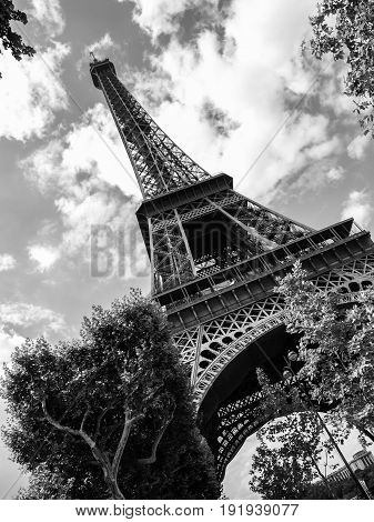 Bottom view of Eiffel Tower on sunny summer day, Paris, France. Black and white image.