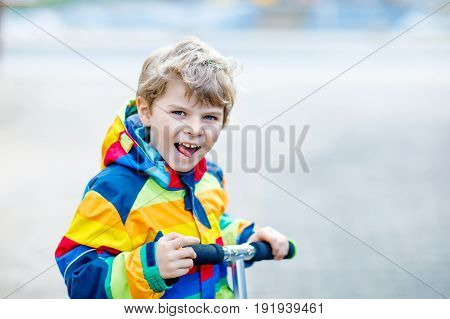 Active school kid boy in colorful casual clothes riding with his scooter in the city. Happy child in colorful clothes biking on way to school. or nursery kindergarten Safe way for kids to school.