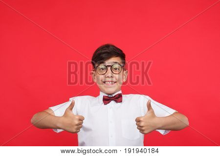 Boy in glasses and shirt smiling at camera and holding thumbs up on red background.