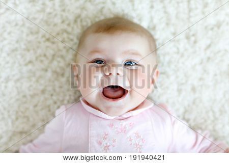 Close-up of a two or three months old baby girl with blue eyes. Newborn child, little adorable smiling and attentive girl looking surprised at the camera. Family, new life, childhood concept