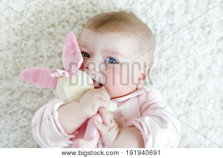 Cute adorable newborn baby playing with colorful pastel plush bunny toy. New born child, little girl looking at the camera. Baby learning grab