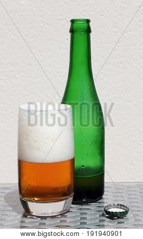 Green bottle of beer in the back with drops and a glass of beer in the front with drops and foam.