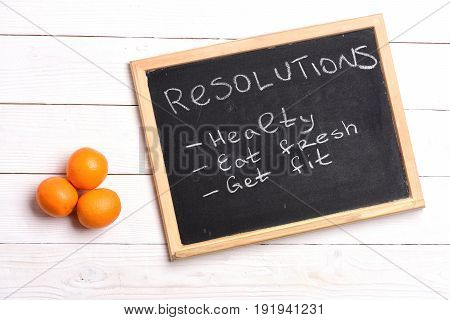Chalkboard with resolutions like healthy eat fresh and get fit lying on white wooden background near orange fruit top view. Diet plan and healthy nutrition concept