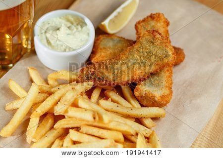 Fried fish and chips on a paper tray - Natural wooden background. beer on backround