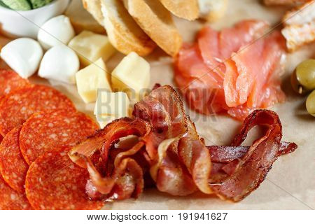 Arrangement of delicatessen cold cuts with smoked ham, pepperoni, salami, green olives, mozzarella cheese, masdam, salted salmon and bread, cheese closeup on wooden background