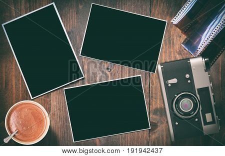 Old retro camera with black photographs on vintage wood tables