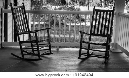 Two Empty Rocking Chairs. Two wooden rocking chairs on a front porch on a warm summer evening.