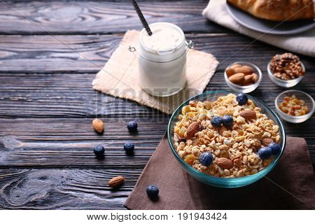 Delicious muesli with berries and almonds on wooden table