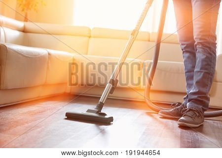 Low section of man cleaning hardwood floor with vacuum cleaner