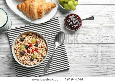 Delicious corn rings with grapes and berries on table