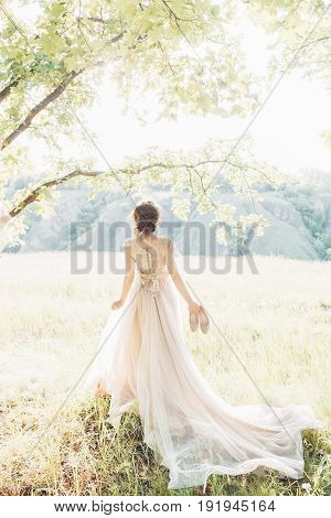 fine art wedding photography. Beautiful bride with shoes and dress with train against the sun in the nature