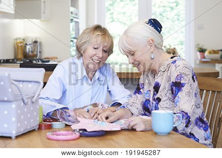 Two Senior Women At Home Sewing Quilt Together