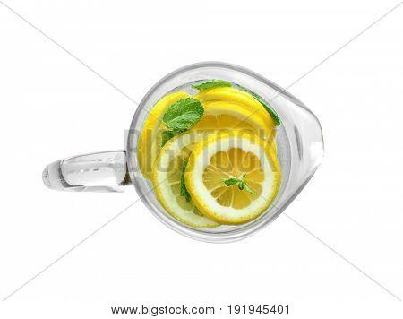 Tasty refreshing lemonade in glass jug on white background