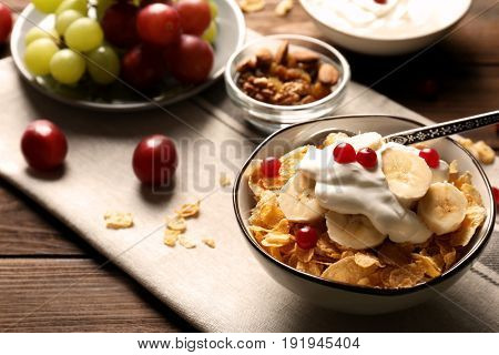Delicious muesli with banana slices, berries and yogurt on table