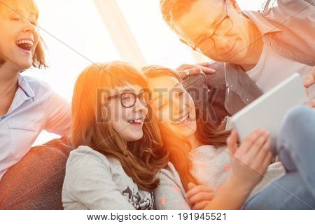 Cheerful family using tablet PC at home