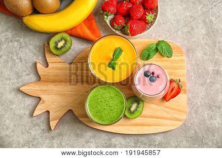 Fresh banana, kiwi and blueberry yogurt smoothies on cutting board