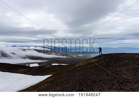 Solitude Landscape In Iceland Mountains. Single Traveler Standing On The Hill And Pointing With Fing