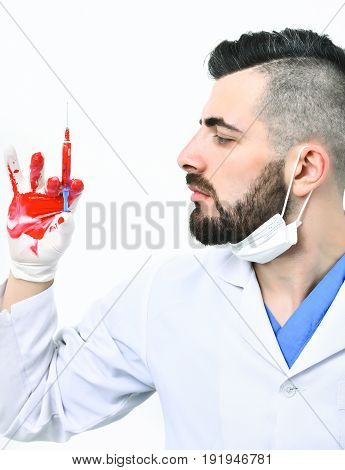 Man In Laboratory Coat Looks At Syringe In His Hand