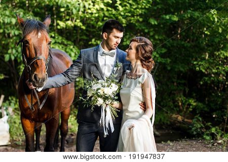 Happy young newlywed couple spends time with the horse.
