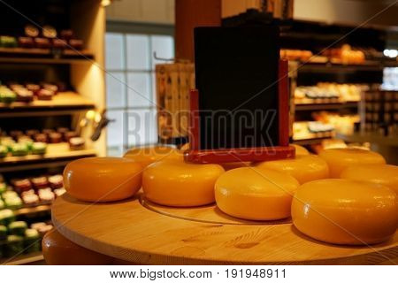 Wheels of cheese on wooden table in store
