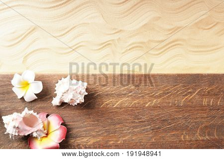 Composition with wooden board, sea shells and flowers on sand. Concept of travel and vacation