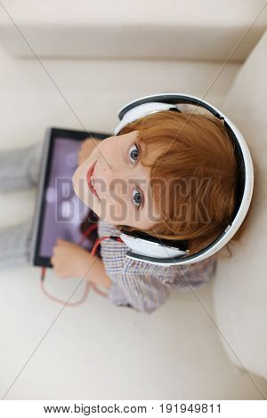 New generation. Adorable bright cute boy sitting on a couch and holding a tablet in his hands while wearing headphones and exploring new videos online