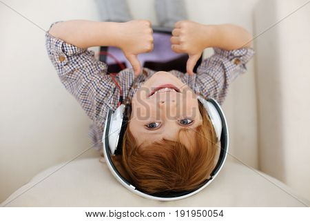 Modern technologies. Diligent charming amusing kid spending day at home and enjoying videos on his tablet while sitting on a couch and wearing headphones