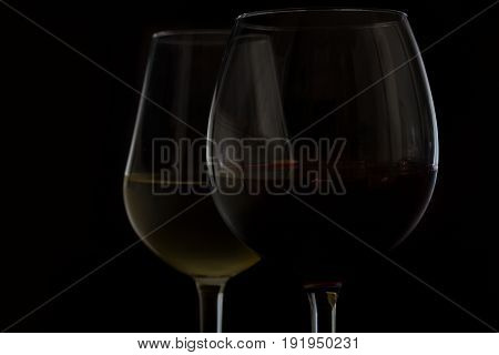 Wine glasses on black - two glasses of red and white wine close up