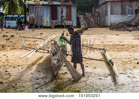 Ambatozavavy Nosy Be Madagascar - December 19 2015: Boatman and his traditional wood pirogue with outrigger in the fishing Ambatozavavy village on the Nosy Be island Madagascar.