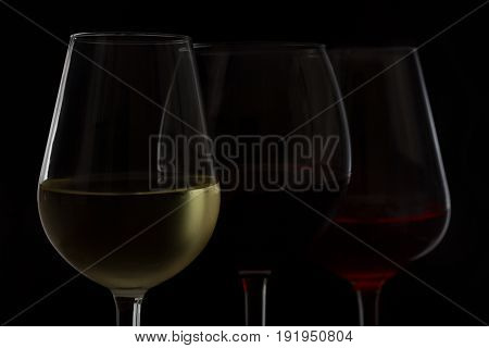 Wine glasses on black - tree glasses of red, rose and white wine close up