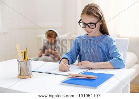 Neat and right. Analytical ambitious gifted child sitting at the table and working on her home assignment while her sibling playing with tablet on a couch behind her