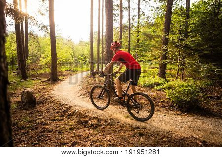 Mountain biker riding on bike in spring inspirational mountains landscape. Man cycling MTB on enduro trail track. Sport fitness motivation and inspiration. poster