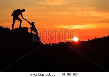 Teamwork couple helping hand trust silhouette in inspiring mountains. Team of climbers assistance man and woman hiker help each other on top of mountain beautiful sunset landscape in Corsica France