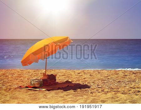 Yellow umbrella on hot sunny sandy beach by blue ocean