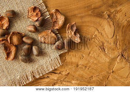 Pine Nuts And A Shuck Closeup On A Napkin From Sackcloth On A Wooden Background.