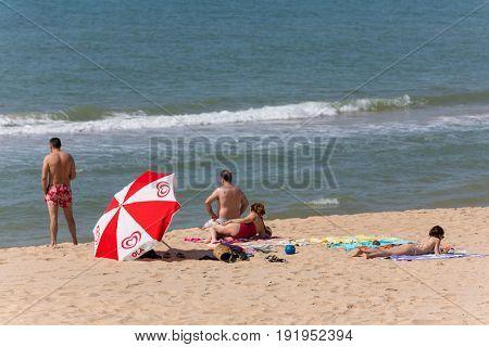 ALVOR, PORTUGAL - APRIL 23, 2017: People at the famous beach of Praia do Alvor, Algarve region, Portugal