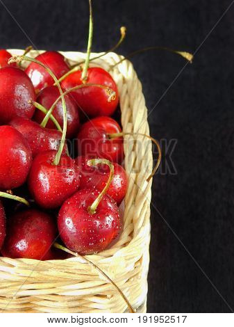 Close-up of cherries in a wicker basket. Empty place for a text