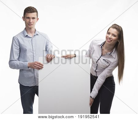 Young happy couple portrait of a confident businessman showing presentation, pointing paper placard gray background. Ideal for banners, registration forms, presentation, landings, presenting concept.