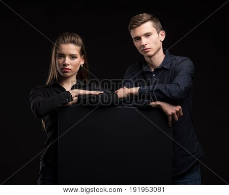 Young confident couple portrait of a confident businessman showing presentation, pointing placard black background. Ideal for banners, registration forms, presentation, landings, presenting concept.