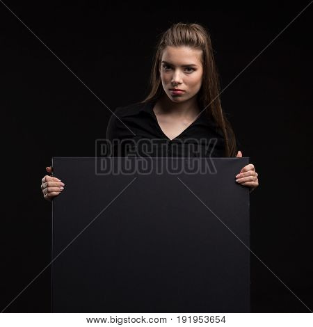 Young sexy woman portrait of a confident businesswoman showing presentation, pointing placard black background. Ideal for banners, registration forms, presentation, landings, presenting concept..
