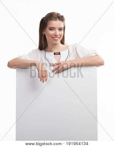 Young sexy woman portrait of a confident businesswoman showing presentation, pointing paper placard gray background. Ideal for banners, registration forms, presentation, landings, presenting concept..