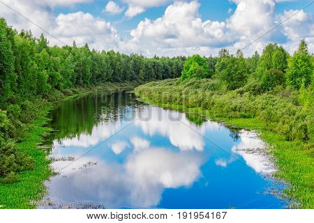 Sky and clouds reflected in the surface of the small river