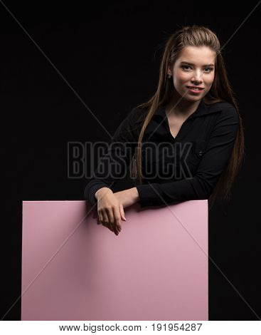Young sexy woman portrait of a confident businesswoman showing presentation, pointing placard pink background. Ideal for banners, registration forms, presentation, landings, presenting concept..