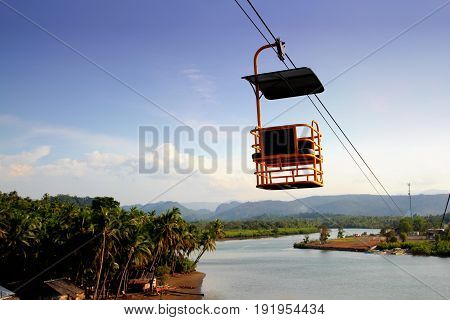 Cable car above the river A cable car glides down thick cables above the river in Carrascal, Surigao del Sur, Philippines.
