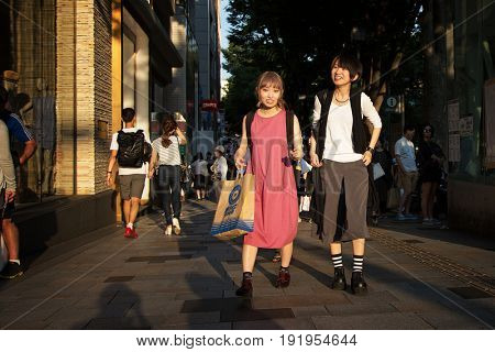 Tokyo, Japan - 26 June 2016:  Stylish female shoppers in the late afternoon sun. Uptown shopping district or Harajuku, near Yoyogi Park, Tokyo.