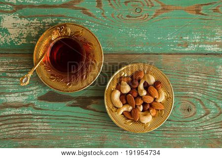 Mixed Nuts On A Yellow Metal Saucer And A Glass Cup Of Turkish Tea On A Turquoise Wooden Background,