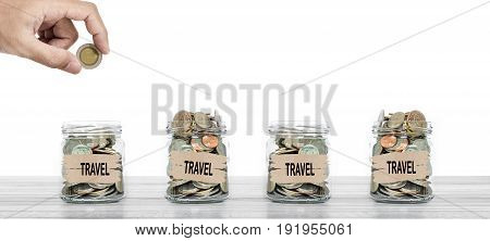 Saving money for traveling, Hand putting coin in glass bottles