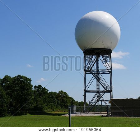 Doppler weather radar at a weather station A huge white Doppler weather radar sitting on top of a steel structure outside a weather station
